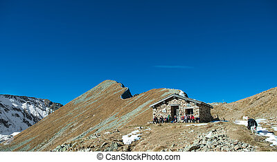 group of trekkers rest in a hut under the mountain with dog