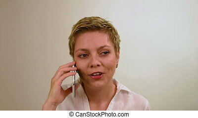 Young excited blond girl talking by mobile phone