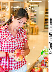 Portrait of a young girl with apples in the store