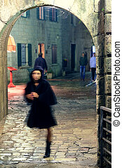 Blurred silthouette of a girl, going from a stone arch