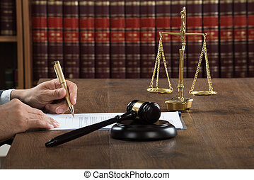 Judge Writing On Legal Documents At Desk - Cropped image of...