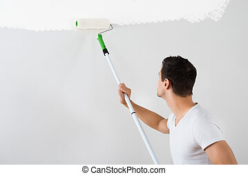 Man Painting Wall With Paint Roller - Side view of young man...