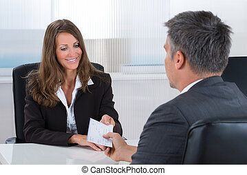Businesswoman Giving Cheque To Businessman - Happy...