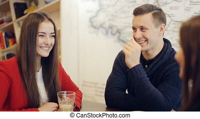 boy and two girls laughing and talk in cafe - guy and two...