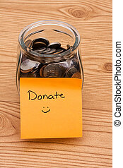 Please help by donating money - A jar full of change sitting...