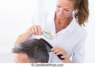 Dermatologist Looking At Patient's Hair - Female...
