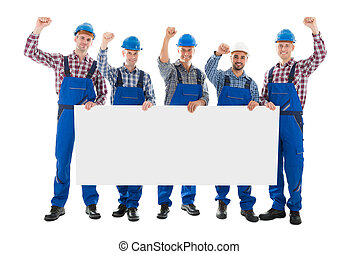 Male Carpenters With Arms Raised Holding Blank Billboard -...