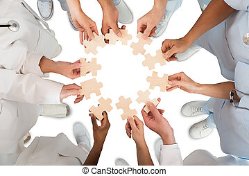 Medical Team Holding Jigsaw Pieces In Huddle - Directly...