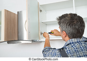 Serviceman Fixing Cabinet With Screwdriver In Kitchen - Rear...