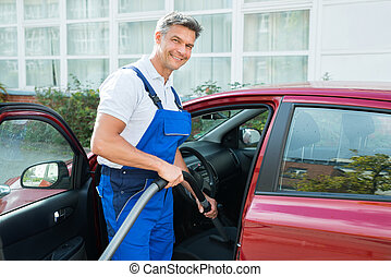 Happy Worker Vacuuming Car Seat With Vacuum Cleaner