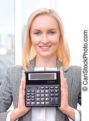 Pleasant businesswoman holding calculator