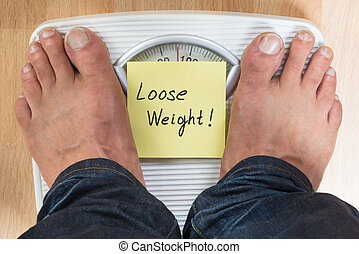 Man Standing On Weight Scale - Low section of man standing...
