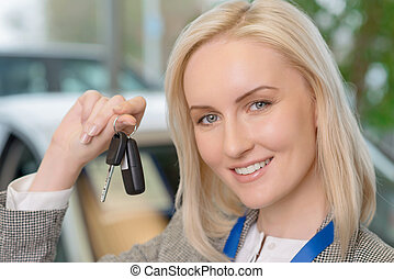 Smiling salesperson presenting a car key - This can be yours...