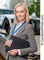 Car salesperson is holding a clipboard. - Charismatic...
