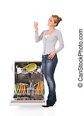 Woman Looking At Clean Glass While Standing By Dishwasher -...