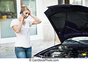 Woman Using Mobile Phone While Looking At Broken Down Car -...