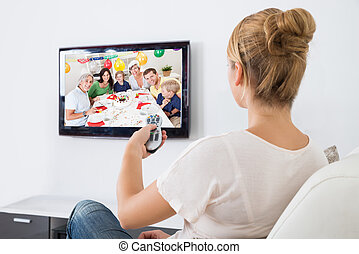 Young Woman Watching Television While Sitting On Sofa -...