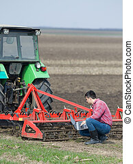 Farmer with laptop and tractor - Young farmer working on...