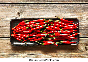 Red hot chili peppers on rustic wooden background