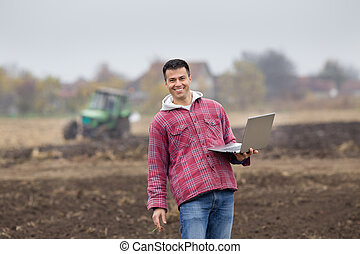 Farmer with laptop - Young farmer with laptop standing on...