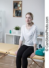 Patient sitting on physiotherapy plinth - Photo of female...