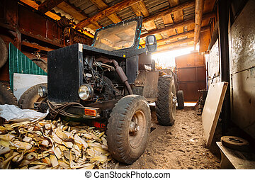 Old homemade tractor stands in barn - Old homemade tractor...