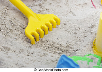 Children's toy rake on the sand