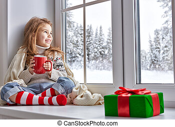 little girl sitting by the window