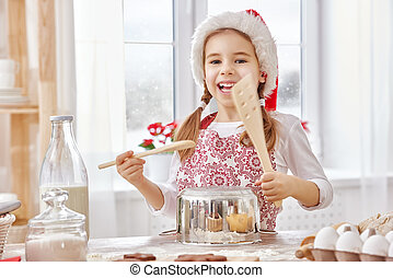 cooking Christmas biscuits - little girl cooking Christmas...