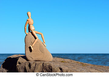 Dummy sitting on the stone - Wooden dummy sitting on the...