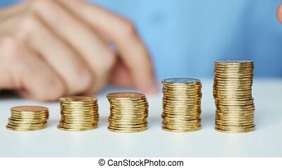 Male hand stacking gold coin