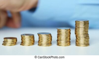 Male hand stacking gold coin - Savings, male hand stacking...