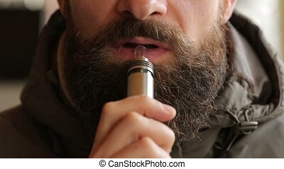 man smoking electronic cigarette - Close up of a bearded man...