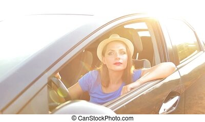 Smiling woman driving a car at sunset Travel concept