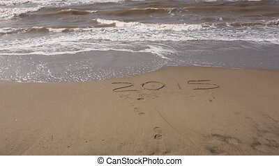sand text 2015 - sea wave deleting 2015 text on sandy shore