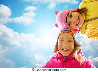 happy little girls faces over blue sky