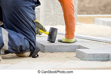 Paving stone - Paver hammering flagstones in sand for...