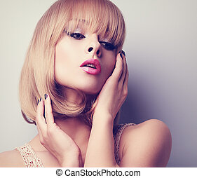 Blond short hair style woman with pink lipstick posing. Toned closeup portrait