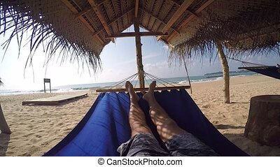 pov man in hammock in the shade of palmtrees on tropical beach