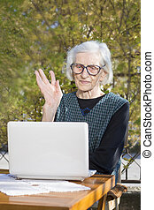 Senior woman having a video call on a notebook computer in...