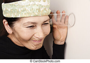 Woman overhears - Middle aged woman listening in to a...