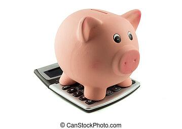Piggy bank on top of calculator - A piggybank standing on...