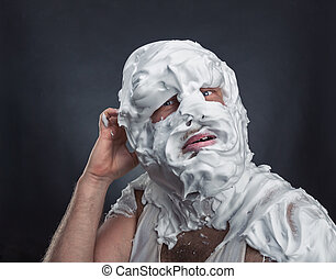 Crazy man with face completely in shaving foam thinks over...