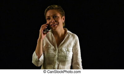 Short hair girl talking by mobile phone over black - Short...