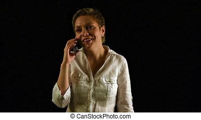 Short hair girl talking by mobile phone over black - Short...