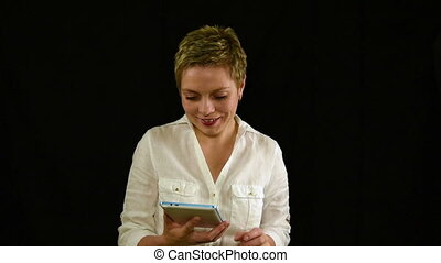 Pretty smiling young woman texting by tablet pad