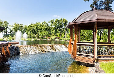 Beautiful lake in spring park with wooden summer-house