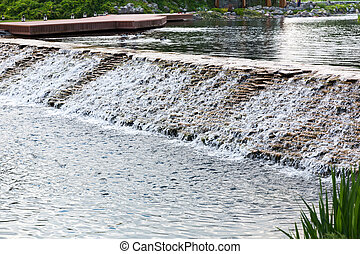 Beautiful lake with little waterfall in summer park