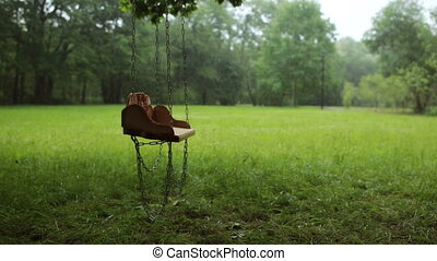 Empty wooden swing swaying slowly in the rain
