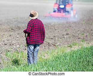Farmer looking at tractor on field - Rear view of farmer...